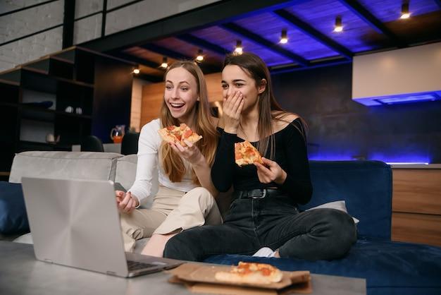 Замедленное движение удивленных привлекательных стильных подруг 25-х годов, которые сидят на удобном диване и наслаждаются вкусной пиццей во время просмотра забавных картинок на компьютере