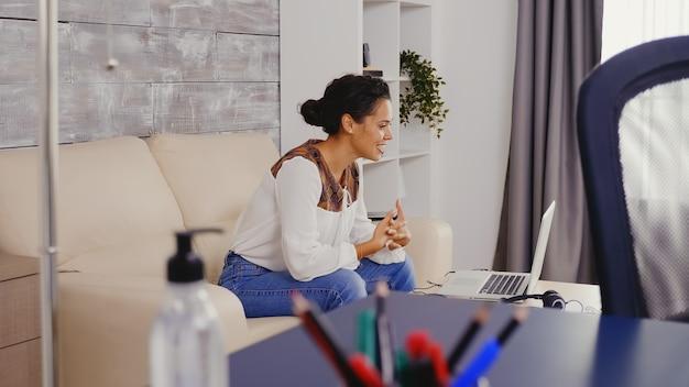 Медленное движение выстрел женщины улыбается во время видеозвонка, сидя на диване.