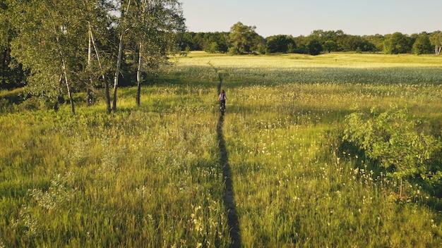 緑の草の牧草地で自転車に乗るスローモーションの女性晴れた日の夏の自然の風景緑豊かな
