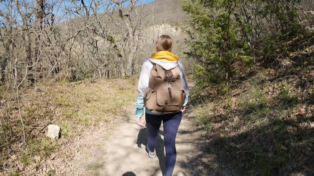 슬로우 모션: 숲에서 하이킹 하는 젊은 여자. 나무를 들고 배낭과 활성 건강한 백인 여자. 에프