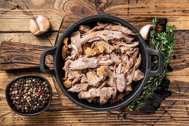 Медленно измельченные пули свинины на сковороде с мясным ножом. деревянный