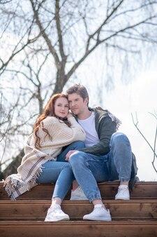 スローダウン、自然。自然の中で階段に座っている格子縞の若い大人の男性と女性を抱きしめる物思いにふける