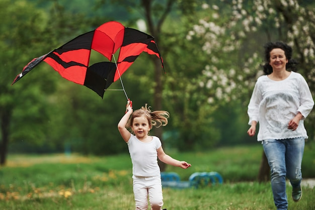 Slower, please. positive female child and grandmother running with red and black colored kite in hands outdoors