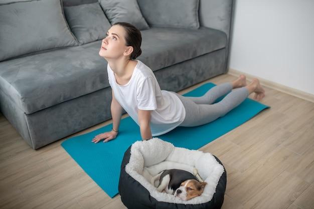 Замедление. молодая женщина, тренирующаяся, пока ее щенок спит рядом