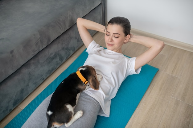 Slowing down. a young woman having a workout with her puppy