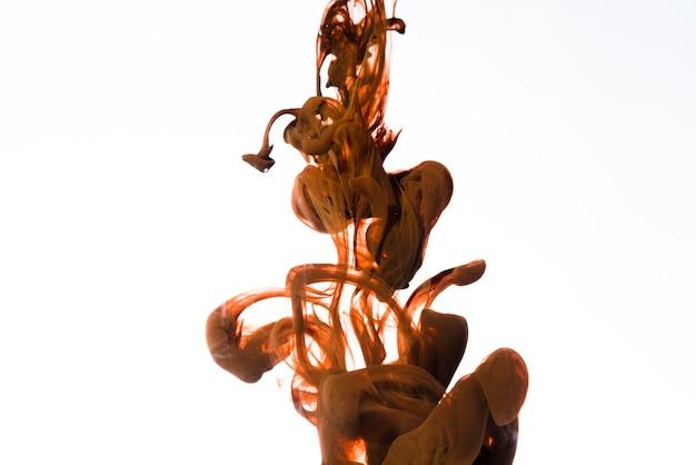 Goccia d'inchiostro marrone che cade lentamente
