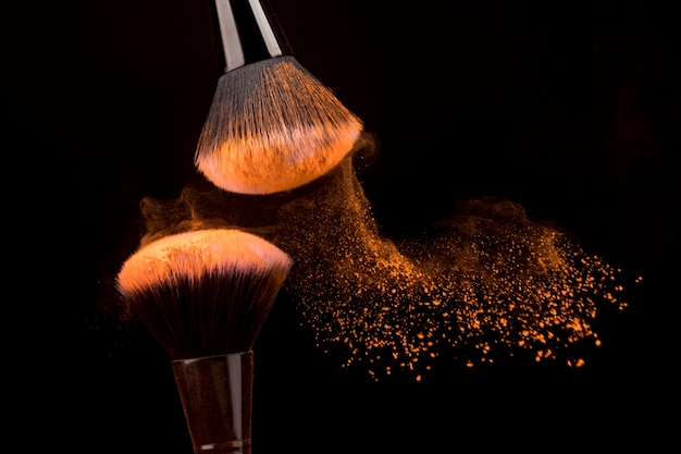 Slowly flying particles of orange powder from brushes