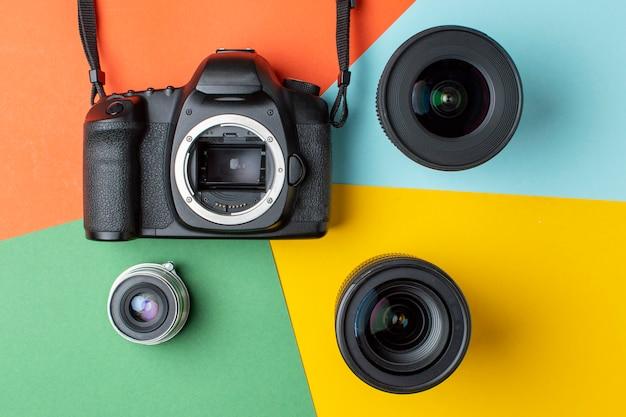 色付きの背景にさまざまなレンズのセットを持つ一眼レフカメラ