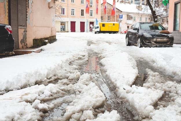 道路上で雪と泥が混ざった雪。道路は雪が降っていません。