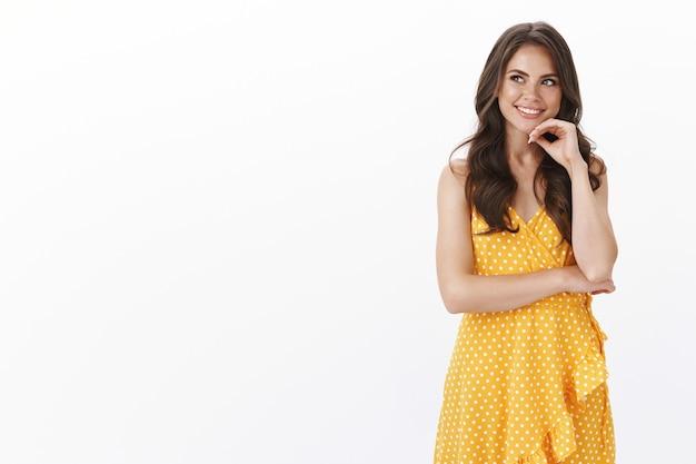 トレンディな黄色のサマードレスを着た、魅力的な白人の若い女性モデル、あごに触れて軽薄、不思議な笑顔、興味をそそられるコピースペースを見て、興味を持って考え、白い壁に立つ