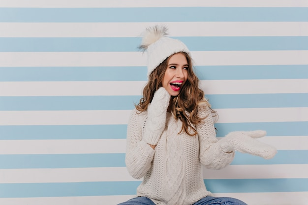 Sly, funny white model playfully with laugh looking to right. portrait of woman sitting on floor in winter clothes indoors