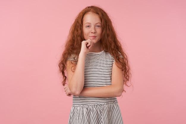 Хитрая милая рыжая девочка с кудрявыми волосами в полосатом платье, держащая подбородок поднятой рукой и положительно смотрящую в камеру с нежной улыбкой, изолирована на розовом фоне