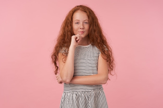 Sly lovely redhead female kid with curly foxy hair wearing striped dress, holding her chin with raised hand and looking positively to camera with gentle smile, isolated over pink background