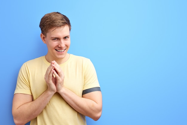 Sly man in casual wear rubbing palm as having cunning evil idea, devious plan in mind, thinking revenge. indoor studio shot isolated on blue background Premium Photo