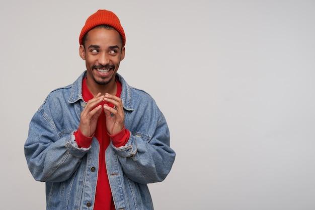 ずるい若い魅力的なひげを生やしたブルネットの男性、暗い肌は思慮深く脇を見て、狡猾に微笑んで、白い壁に赤い帽子、プルオーバー、ブルージーンズのコートを着ています