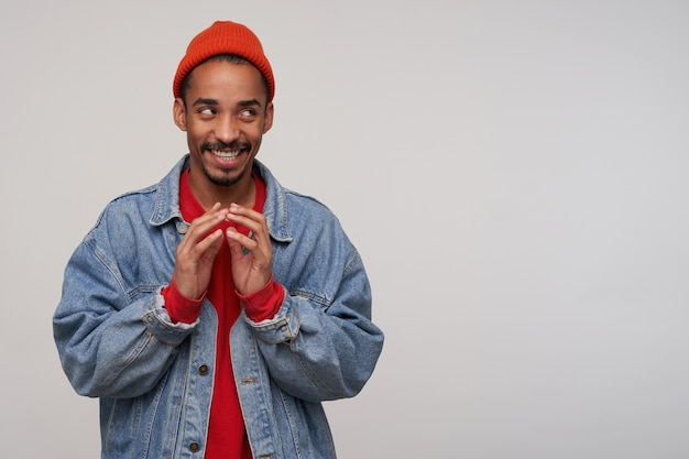 Sly young attractive bearded brunette male with dark skin looking aside thoughtfully and smiling cunningly, wearing red cap, pullover and blue jeans coat over white wall