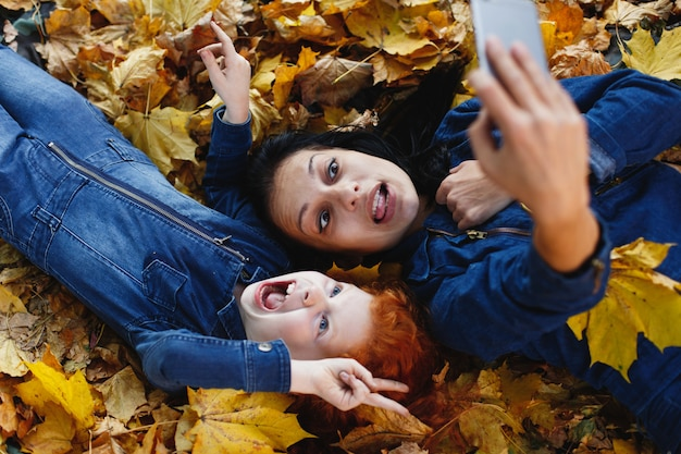 秋の雰囲気、家族の肖像画。魅力的なママと彼女の赤い髪の娘はsmにselfieを取って楽しんでいます