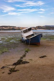 Маленькая заброшенная рыбацкая лодка на пляже комбарро в галиции