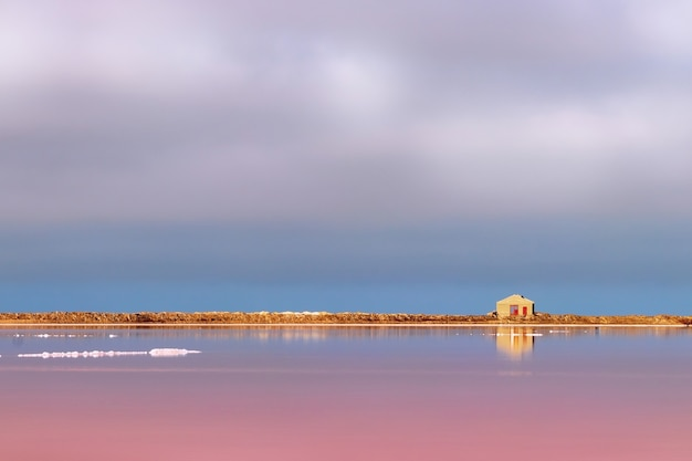 A small abandoned stone house stands on a pink salt lake under a bright blue sky