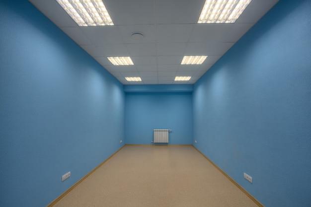 小さな放棄された家具のないオフィス、ボディ、窓はなく、壁は青く塗られています。