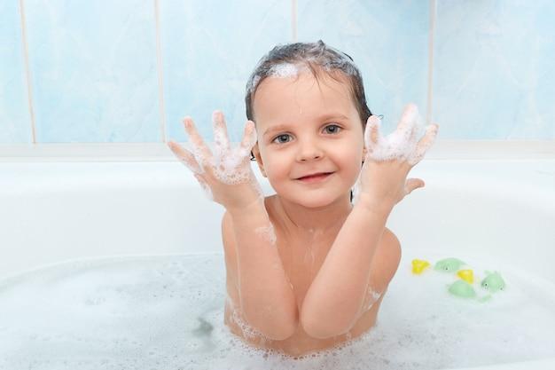 Маленький очаровательный ребенок с забавным выражением лица, с удовольствием принимает ванну, играет в горячей воде и показывает руки с пеной, позирует в ванной