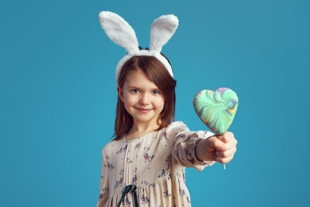 Маленькая очаровательная девочка держит печенье в форме сердца с кроличьими ушками