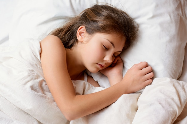 Small adorable girl lies on comfortable bed having good pleasant dreams resting after a hard day of studying at school