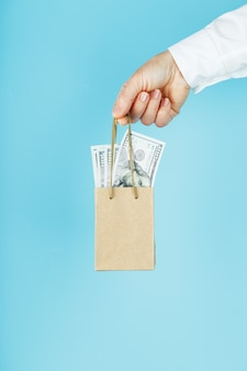 A small aid bag made of paper in an outstretched hand with us dollars on a blue background. packaging template layout with space for copying, advertising.