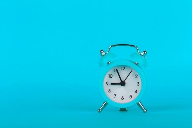 Small alarm clock on blue background
