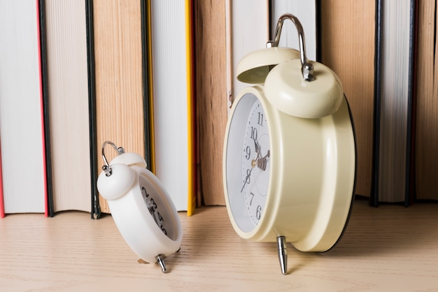 Small alarm clock in front of large clock in front of bookshelf on wooden desk