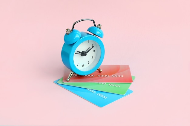 Small alarm clock lies on colored credit cards