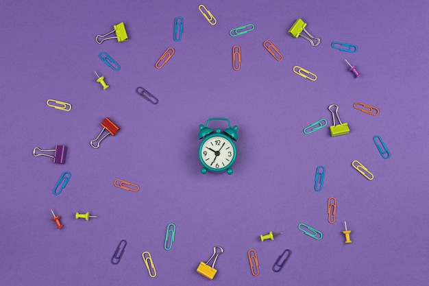Small alarm clock on a purple background with paper clips