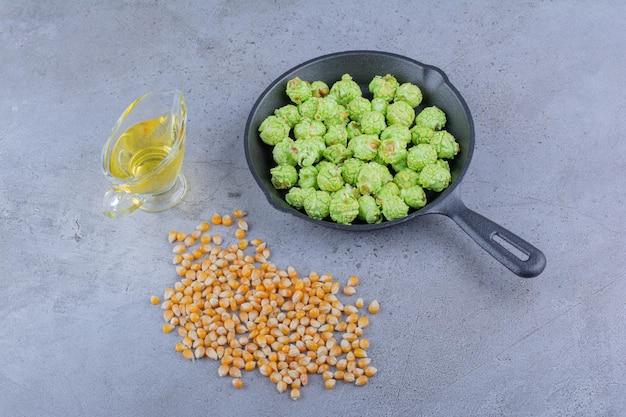 Небольшое количество кукурузных зерен, стакан масла и сковорода с засахаренным попкорном на мраморной поверхности.