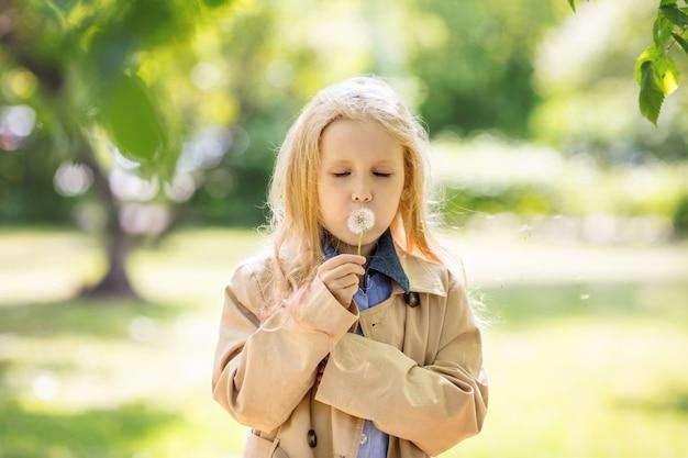 自然の中で彼女の手にタンポポの花で甘くて幸せな小さくて美しい女児