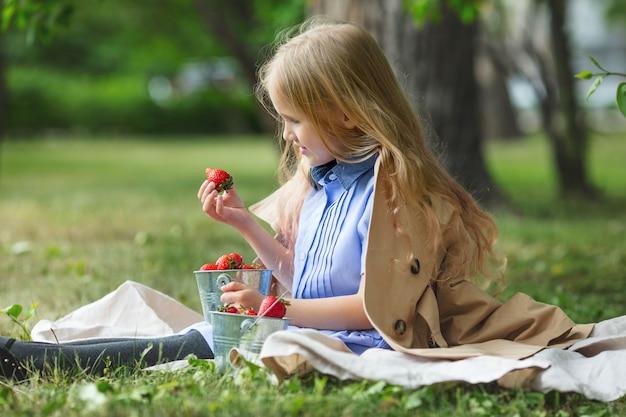 自然の中で彼女の手にイチゴと甘くて幸せな小さくて美しい女児