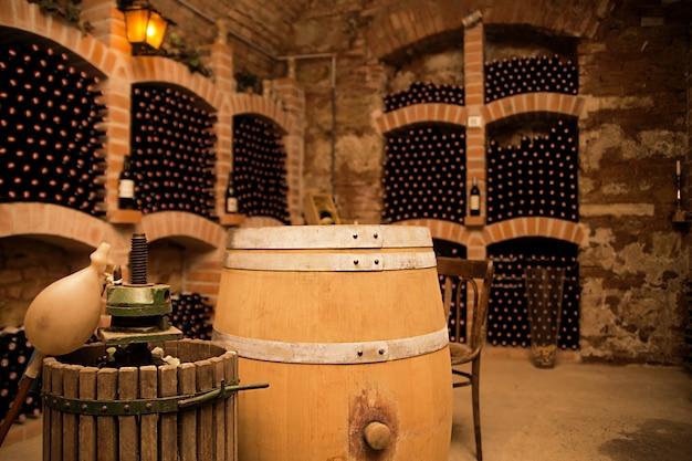 Маленький и старый винный погреб с множеством полных бутылок и кег
