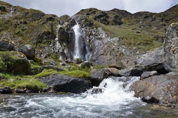 雪に覆われた緑からアンデスの小さな滝