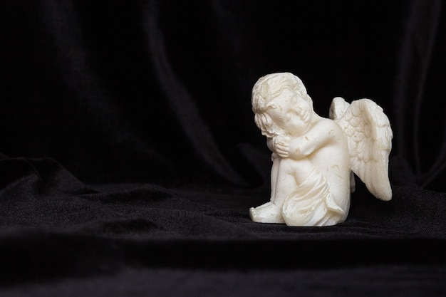 Small angel with wings on a black background, free space for text