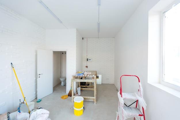 新しい建物の修理のない小さなアパート。未完成の家の部屋。小さなアパートのフォームブロックとコンクリートの床の壁。