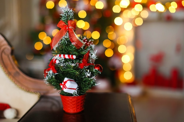 Small artificial christmas tree on the background of bright yellow garlands and christmas tree.