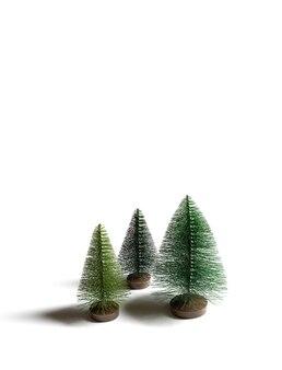 白い背景で隔離の小さな人工的なクリスマスツリー。垂直方向。