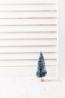 Small artificial fir with wooden window background