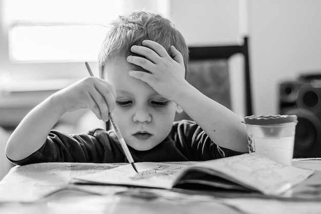 Маленький художник. черно-белая фотография. маленький мальчик рисует раскраски.