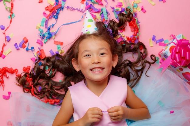 小さなアジアの女の子、誕生日の帽子、笑顔、ギフト、紙吹雪、仰向けになって、トップビュー、