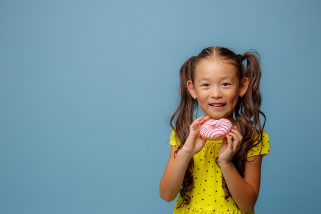 A small asian girl with long hair holds a doughnut in her hands and smiles at the studio on a blue