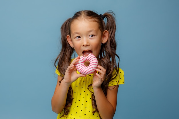 A small asian girl with long hair holds a doughnut in her hands and smiles