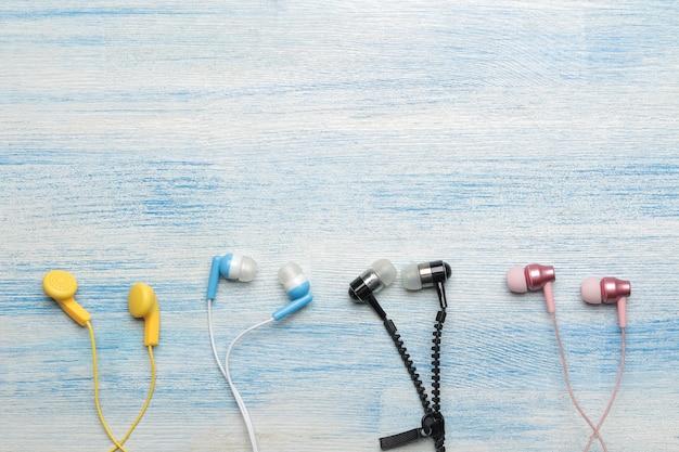 밝은 파란색 나무 배경에 작은 여러 가지 빛깔의 헤드폰. 평면도
