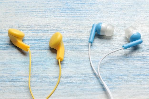 밝은 파란색 나무 배경에 작은 여러 가지 빛깔의 헤드폰.