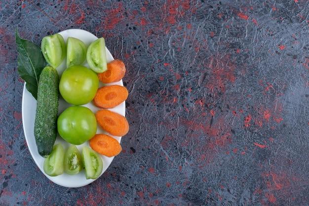 Небольшой ассортимент овощей на блюде на темном фоне. фото высокого качества