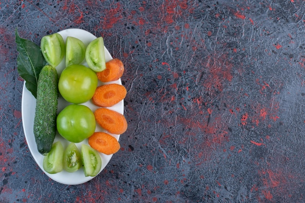 Small assortment of vegetables on a platter on dark colored background. high quality photo